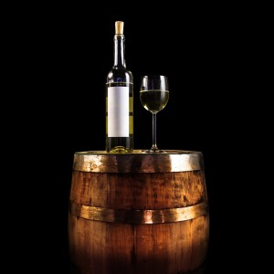 White wine bottle and glass on a wooden barrel